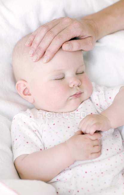 Female hands feeling forehead of baby for measuring temperature. — Stock Photo
