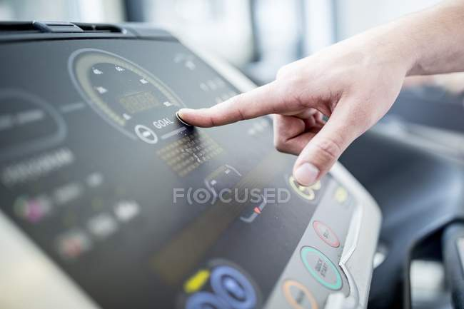 Close-up of male hand pushing control panel button of exercise machine. — Stock Photo
