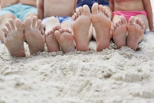 Family sitting on beach with barefoot feet. — Stock Photo