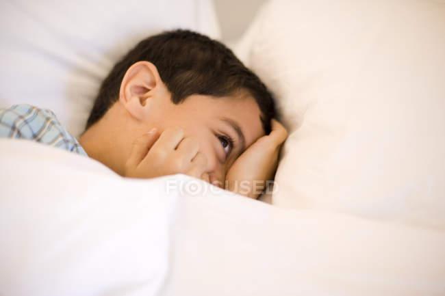 Garotinho divertidamente escondendo o rosto na cama. — Fotografia de Stock