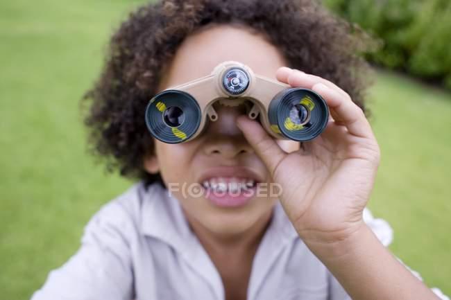 Niño usando prismáticos en el parque . - foto de stock