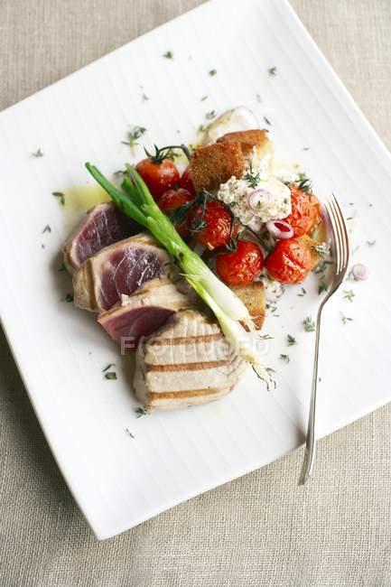 Gesunde Mahlzeit aus gegrilltem Thunfisch, gebratenen Tomaten und Ziegenkäsesalat. — Stockfoto