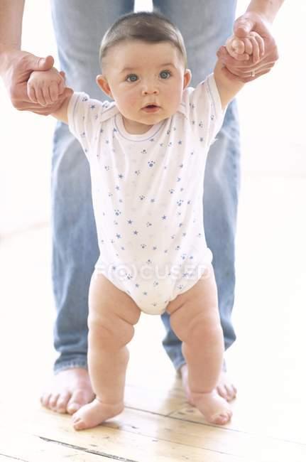 Bambino neonato sostenuto dal padre sul pavimento . — Foto stock