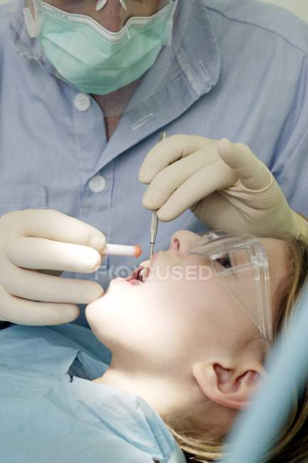 Dentist performing dental treatment on young girl. — Stock Photo