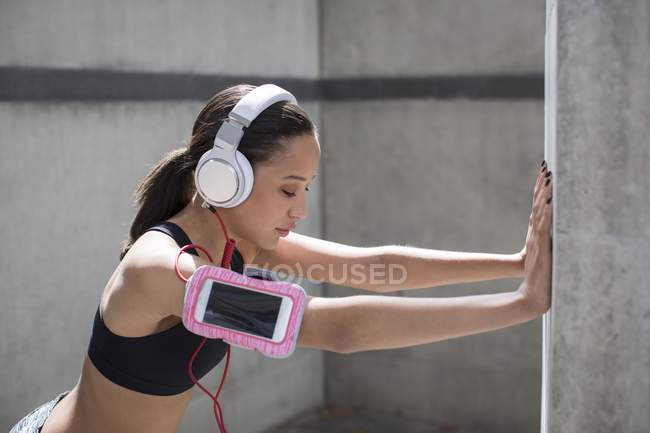 Woman wearing headphones and stretching against wall — Stock Photo