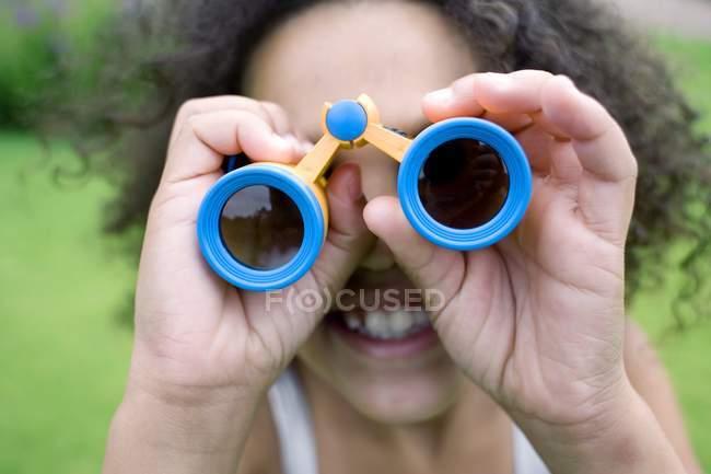 Chica afrocaribeña usando prismáticos en el parque . - foto de stock