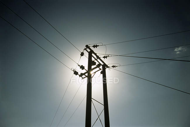 Wooden pylon supporting power lines against sunlight. — Stock Photo