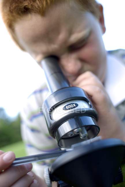 Niño pelirrojo usando microscopio de luz para estudiar en el prado . - foto de stock
