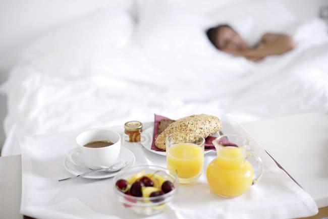Vassoio di caffè, succo e frutta accanto alla donna addormentata . — Foto stock