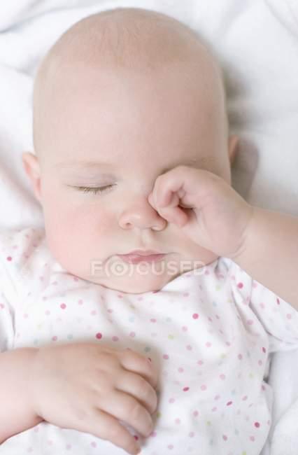 Младенческой ребенка трения глаз в постели. — стоковое фото