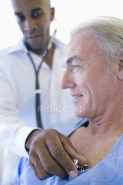 Doctor using stethoscope and listening to patient chest. — Stock Photo