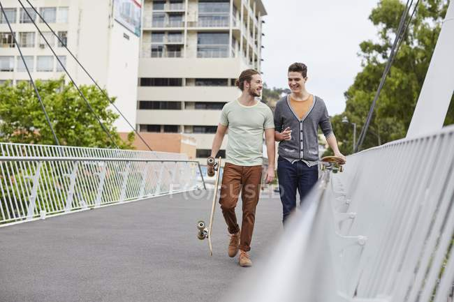 Two young men walking with skateboards on street. — Stock Photo