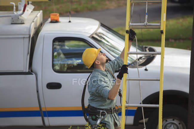 Lineman placing ladder at power pole. — Stock Photo