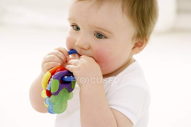 Portrait of baby boy chewing on teething ring. — Stock Photo