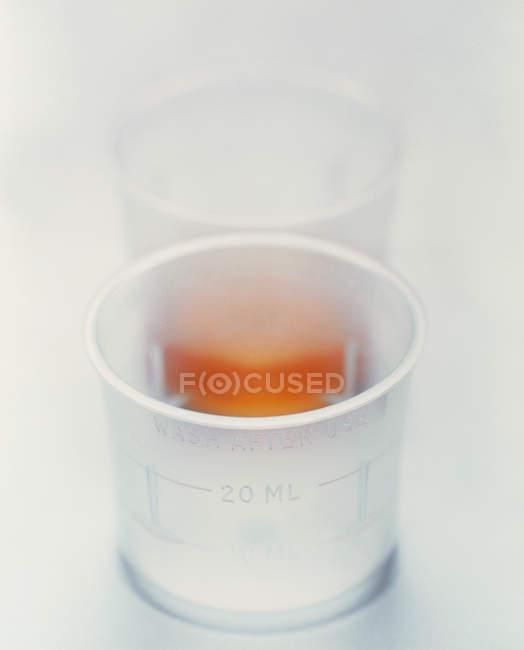Two plastic cups, one containing liquid medicine. — Stock Photo