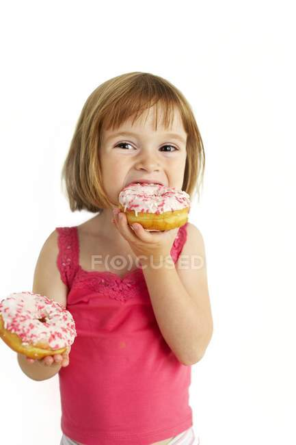 Niña preescolar comiendo donas sobre fondo blanco . - foto de stock