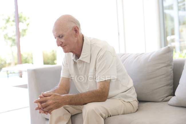 Ältere Mann sitzt allein auf sofa. — Stockfoto