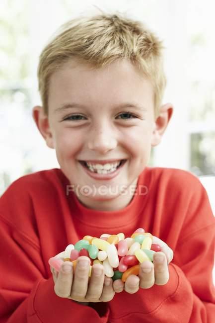 Веселый мальчик держит сладости в руках . — стоковое фото