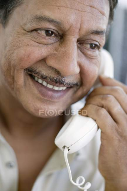 Portrait of smiling mature man talking on corded telephone. — Stock Photo