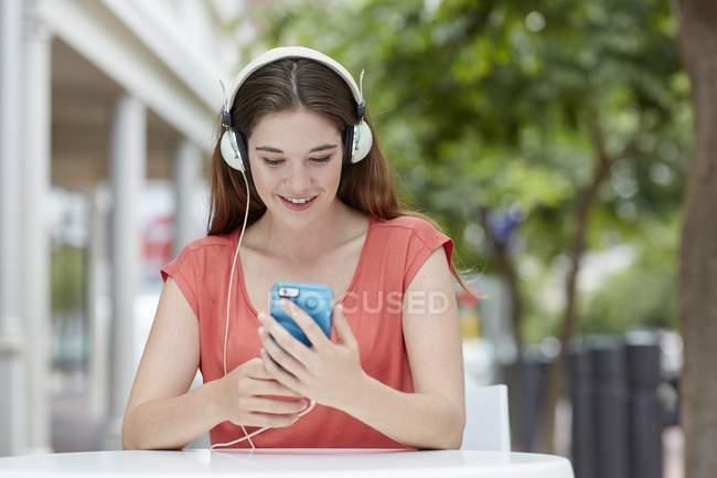 Frau trägt Kopfhörer und anhören von Musik auf smartphone — Stockfoto
