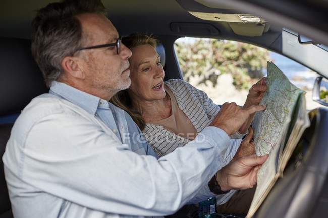Senior couple traveling by car and reading map. — Stock Photo