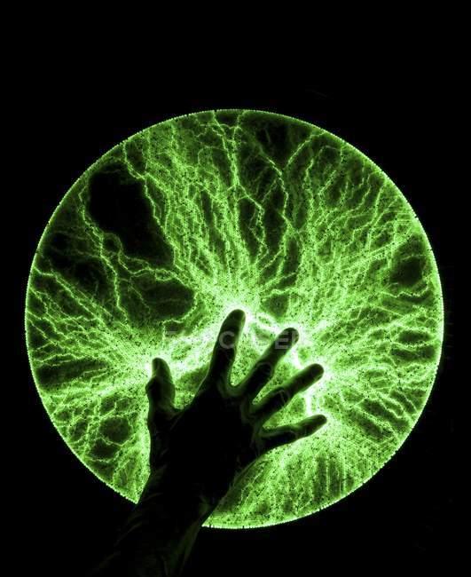 Mão masculina em disco de plasma produzindo pisca verde brilhante. — Fotografia de Stock