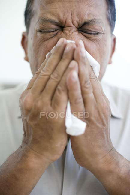 Mature man sneezing into handkerchief. — Stock Photo