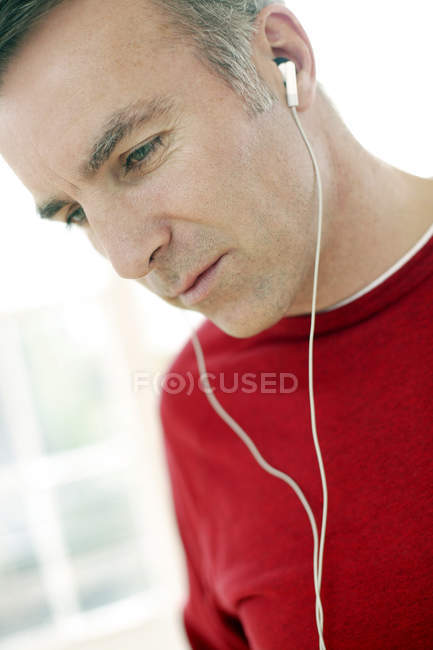 Man listening to music through earphones. — Stock Photo