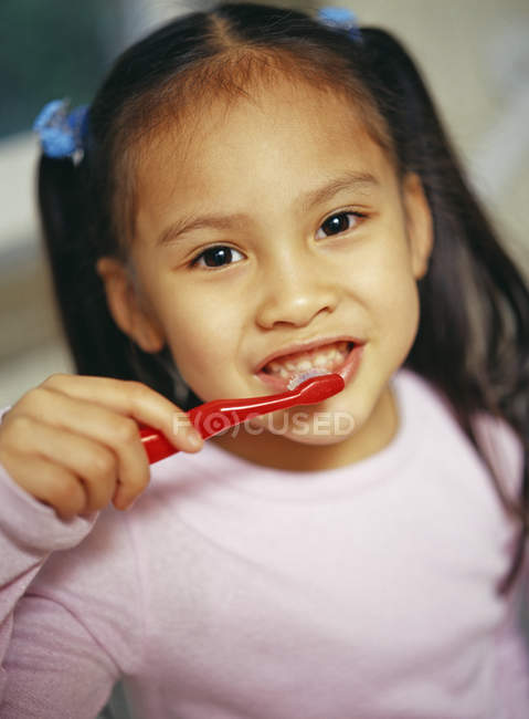 Young girl brushing  teeth to prevent tooth decay — Stock Photo