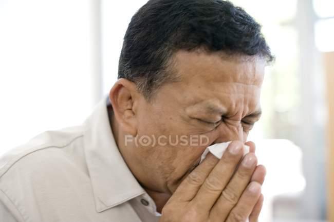 Mature man sneezing into handkerchief. — Stock Photo