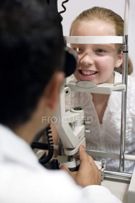 Оптик, використовуючи щілини лампа для очей експертиза предподростковий дівчина. — стокове фото