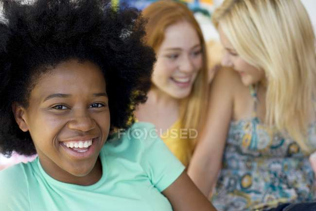Three cheerful teenage girls hanging out indoors. — Stock Photo