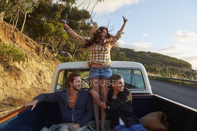 Друзі, їзда в забрати вантажівка з розкритими обіймами. — стокове фото
