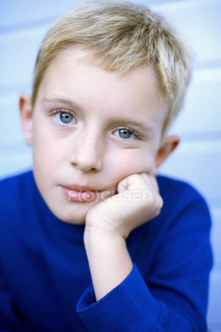 Portrait of pensive boy in blue t-shirt with hand on chin. — Stock Photo