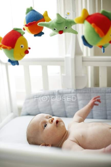 Infant baby boy lying in cot and looking up at toys. — Stock Photo