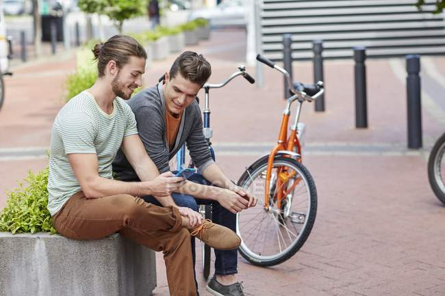 Young men sitting on street wall with smartphone. — Stock Photo