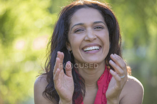 Portrait of happy Hispanic woman clapping in park. — Stock Photo