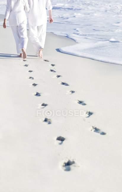 Пара, ходьба пешком на пляж песок с следы. — стоковое фото