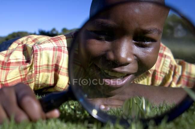 Junge mit Lupe auf dem Rasen. — Stockfoto