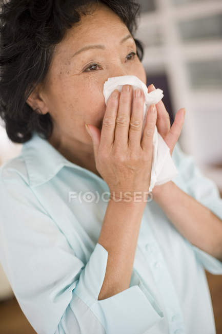 Asian mature woman blowing nose. — Stock Photo