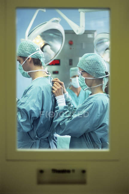 Nurse assisting surgeon and tying protective clothing behind door. — Stock Photo
