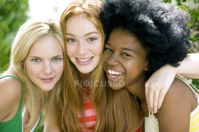 Three cheerful teenage girls hanging out outdoors. — Stock Photo