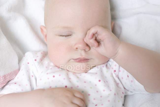 Infant baby rubbing eye in bed. — Stock Photo