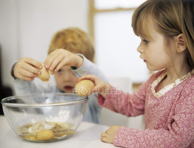 Дети дошкольника, растрескивание яиц в миске. — стоковое фото