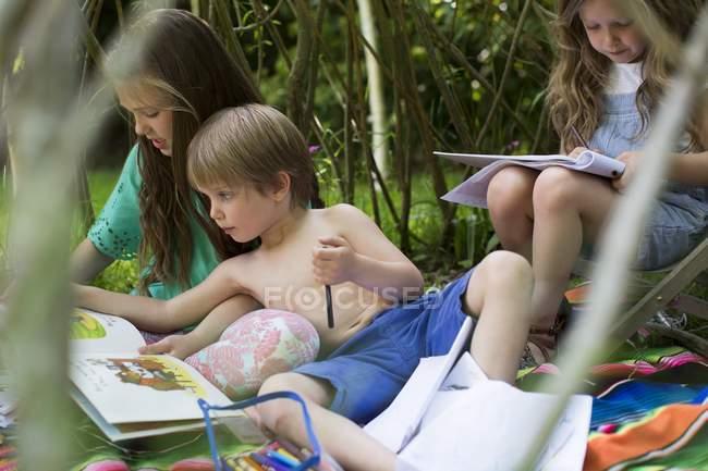Дівчинки і хлопчи читання разом грають у саду Ден. — стокове фото