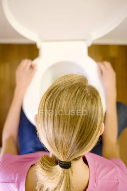 Overhead view of young woman crouching over toilet bowl. — Stock Photo