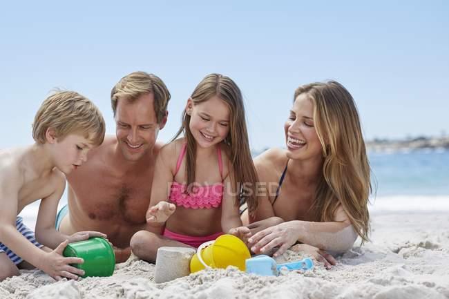 Famiglia con due bambini sdraiati sulla spiaggia . — Foto stock