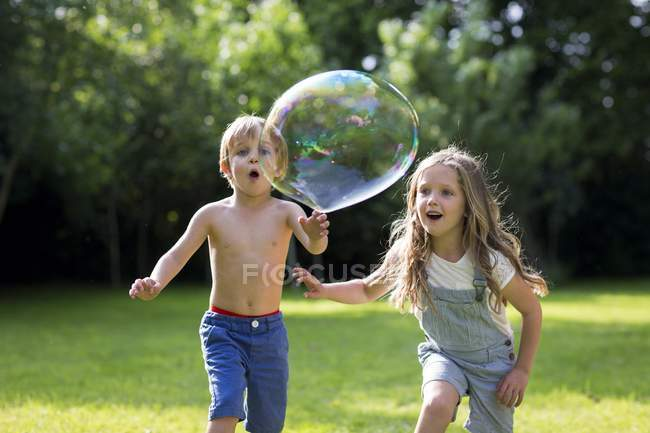 Brother and sister chasing bubble in garden. — Stock Photo