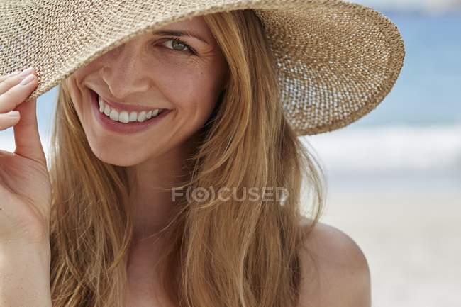 Porträt einer Frau mit Sonnenhut am Strand. — Stockfoto