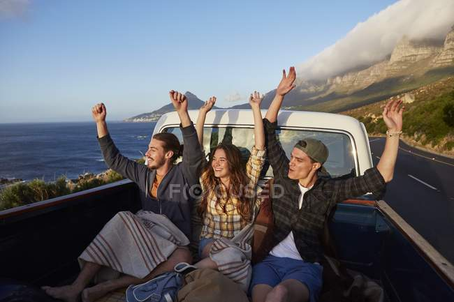 Friends riding in pick up truck with arms outstretched. — Stock Photo